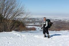 Mann, der aufwärts im Schnee wandert Stockbild