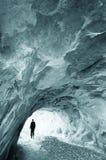 Mann, der aus einer Höhle heraus geht Stockbild