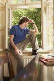 Mann, der aus Fensterbrett im Studien-Raum heraus schaut Lizenzfreie Stockfotografie