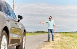 Mann, der Auto an der Landschaft per Anhalter fährt und stoppt Lizenzfreies Stockbild
