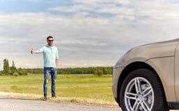 Mann, der Auto an der Landschaft per Anhalter fährt und stoppt Lizenzfreies Stockfoto