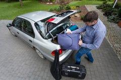 Mann, der Auto für eine Reise vorbereitet Stockbild