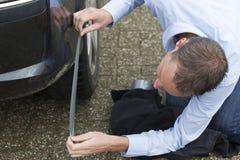 Mann, der Autokarosserie auf Band aufnimmt Stockbild