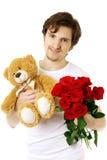 Mann, der Bären und einen Blumenstrauß der Rosen gibt Lizenzfreie Stockbilder