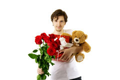 Mann, der Bären und einen Blumenstrauß der Rosen gibt Stockbilder