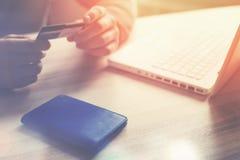 Mann, der Bankkarte hält Laptop und Geldbörse auf dem Tisch Laptop auf weißem backgraund Lizenzfreies Stockbild