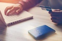 Mann, der Bankkarte hält Laptop und Pass auf dem Tisch Netzeinkaufen Lizenzfreie Stockbilder