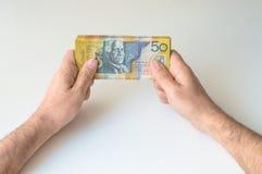 Mann, der Banknote des australischen Dollars fünfzig hält Stockbild