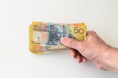 Mann, der Banknote des australischen Dollars hält Lizenzfreies Stockbild
