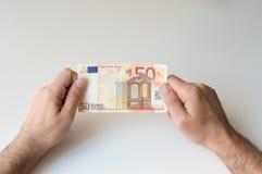 Mann, der Banknote des Euros fünfzig hält Stockfotografie