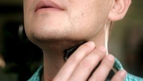 Mann, der Bart mit elektrischem Rasierapparat rasiert Überprüfen Sie das Rasieren, Ihren Finger auf der Backe klauend nahaufnahme stock video