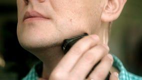 Mann, der Bart mit elektrischem Rasierapparat rasiert Überprüfen Sie das Rasieren, Ihren Finger auf der Backe klauend nahaufnahme stock footage