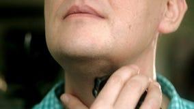 Mann, der Bart mit elektrischem Rasierapparat rasiert Überprüfen Sie das Rasieren, Ihren Finger auf der Backe klauend nahaufnahme stock video footage