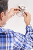 Mann, der Batterie im Hauptrauchmelder ersetzt stockbilder