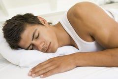 Mann, der beim Bettschlafen liegt Lizenzfreie Stockfotos