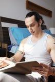 Mann, der beim Buch liegt lizenzfreies stockbild