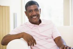 Mann, der beim Wohnzimmerlächeln sitzt lizenzfreie stockfotografie