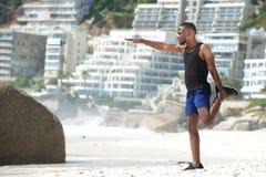 Mann, der Beinmuskeln auf dem Strand ausübt Stockbild