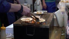 Mann, der berühmte gegrillte Kamm-Muscheln an Kuromon-Markt in Japan, 4K macht stock footage