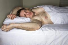 Mann, der in Bett legt Stockbild
