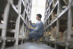 Mann, der am Bibliotheks-Bücherregal sich duckt Stockfoto