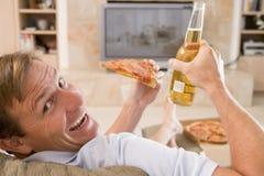 Mann, der Bier und Pizza vor Fernsehapparat genießt Stockbilder