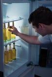 Mann, der Bier von einem Kühlschrank nimmt Lizenzfreie Stockfotos