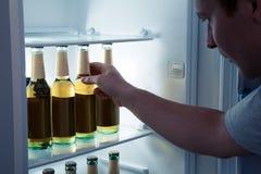 Mann, der Bier von einem Kühlschrank nimmt Stockfotografie