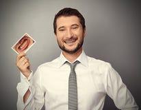 Mann, der Bild mit den gelben Zähnen hält Stockfoto