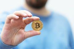Mann, der bitcoin in der Hand hält stockfoto