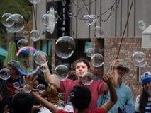 Mann, der Blasen für Menge macht Stockfotos