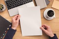 Mann, der Blatt Papier am Arbeitsplatz hält Lizenzfreie Stockfotos
