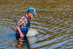 Mann, der blaue Stelzvögel in Kumgang-Fluss trägt Stockfotografie