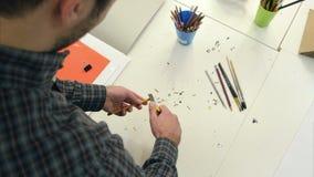 Mann, der Bleistift mit einem Bleistiftspitzer schärft stock video footage