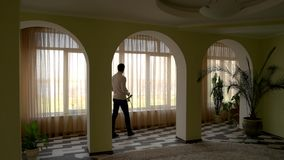 Mann, der Blume nahe Fenster hält stock video