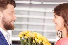 Mann, der Blumen seiner Freundin darstellt Stockbilder