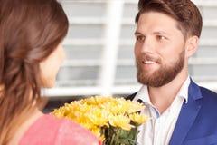 Mann, der Blumen seiner Freundin darstellt Stockbild