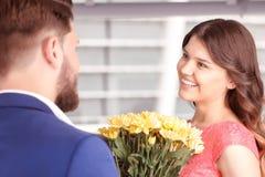 Mann, der Blumen seiner Freundin darstellt Stockfotografie