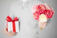 Mann, der Blumenstrauß von Blumen und von Geschenkbox hält Lizenzfreie Stockfotos
