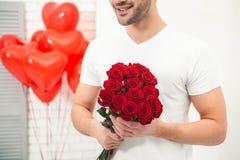 Mann, der Blumenstrauß von roten Rosen hält stockfotos