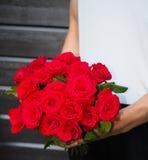 Mann, der Blumenstrauß von roten Rosen hält Stockbild