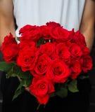 Mann, der Blumenstrauß von roten Rosen hält Stockfotografie