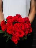 Mann, der Blumenstrauß von roten Rosen hält Lizenzfreies Stockbild