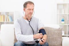 Mann, der Blutdruck überprüft Stockbild