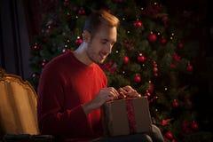 Mann, der Bogen auf Weihnachtsgeschenk bindet Lizenzfreie Stockfotografie