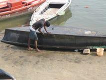 Mann, der Boot Assi Ghat Varanasi India repariert Lizenzfreie Stockfotos