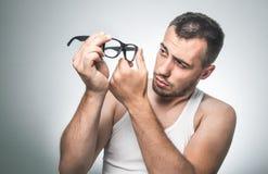 Mann, der Brillen mit seinen Fingern abwischt Stockfotografie