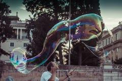Mann, der bunte übergroße Seifenblasen durchbrennt Lizenzfreies Stockfoto