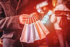 Mann, der bunte Einkaufstaschen auf dem dunklen Stadthintergrund h?lt Effekt Sun-grellen Glanzes, Orange getont lizenzfreies stockfoto