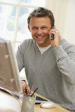 Mann, der Computer verwendet und am Telefon spricht Stockbilder
